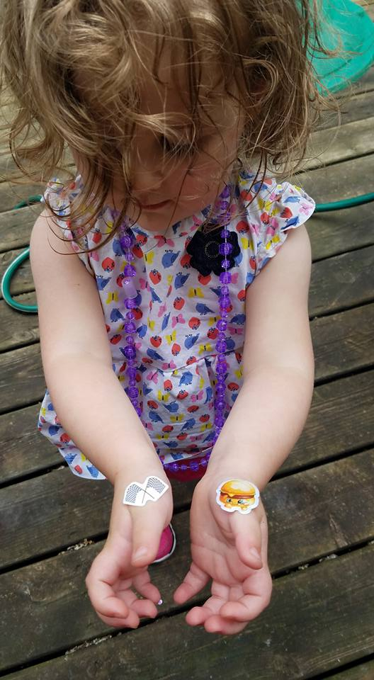 Toddler girl, Little Elfkin, showing racing flag and hamburger stickers