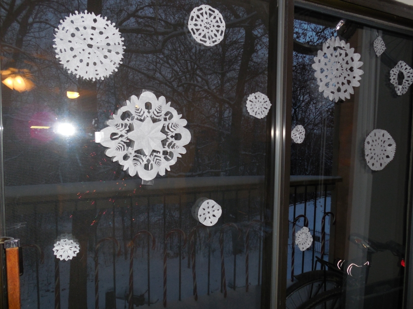 paper snow flakes on a glass door