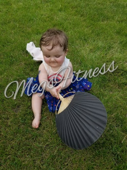 Little Elfkin in an Avengers Dress Playing with a Paper Fan While Sitting in Grass