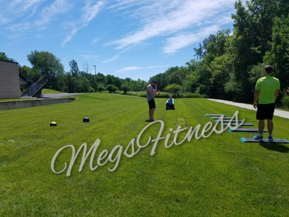 Clear Blue Skies Over a Grassy Field With Bootcamp Stations Set Up and Participants Ready